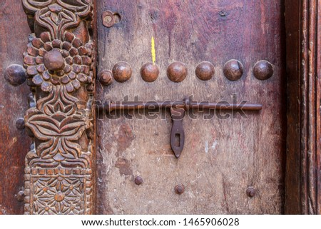 textured detailed section of a wooden door with carved detail and an iron latch for locking and securing the doorway.