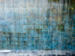Textured geometric tile with waterfall flowing over it