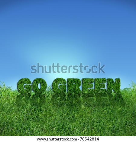 Textured go green sign over fresh grass. Clear blue sky background.