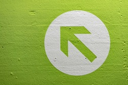 Textured green arrow pointing upwards and to the left.