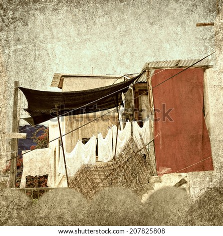 Textured grunge paper background with laundry line and clothes in the old yard of the Mediterranean. Vintage style