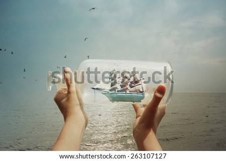 Stock Photo Textured image of a child holding a ship in a bottle at the ocean