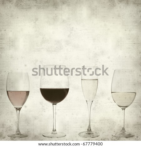 textured old paper background with four different wines in glasses