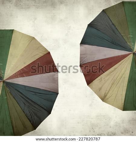 textured old paper background with rainbow umbrella