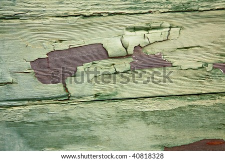 Textured peeling green paint on old weathered wood