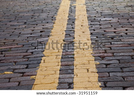 Textured yellow stripes on old brick street