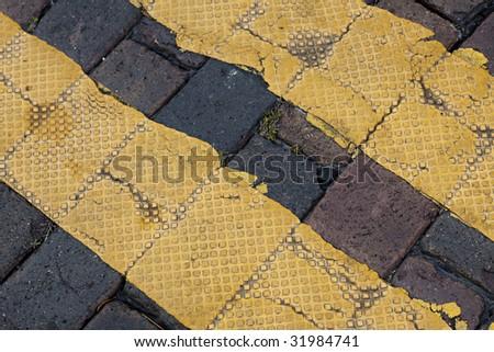 Textured yellow stripes on old brick street