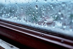 Textures of water droplets of rain flow down the window panel. Condensation, high humidity, cold tone