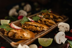 thai and mexican fusion food background of spicy chicken and mushroom tomyum quesadillas on wooden plate in dark tone, selective focused