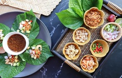 Thai appetizer of food and herb wrapped in leave dipping with sweet sauce in Thai food called Miang Kham - Top view on dark marble background