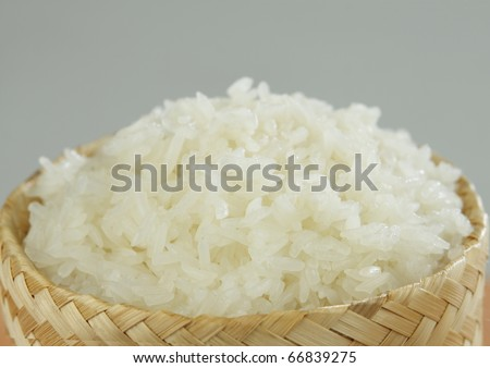 Thai asian sticky rice in a bamboo round basket isolated