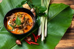 THAI BEEF RED CURRY. Thailand tradition red curry soup with beef  and coconut milk. Red Curry with ingredient in Black plate on  banana  leaf and woodden background.