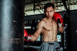 Thai boxer throw an uppercut by his right punch.