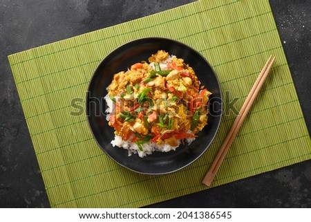 Thai breakfast Gai Pad Pongali with chicken, eggs, spicy, yellow thai curry paste,tomato, rice in black bowl made in wok. Close up. Pan-Asian cuisine. Thai Food Stir Fried.