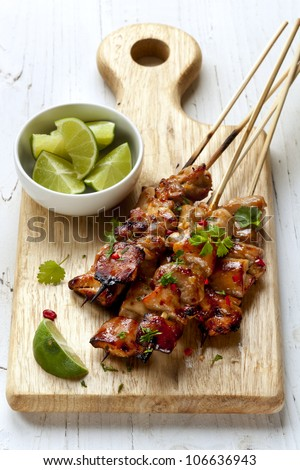 Thai chicken skewers with lime and chili, on wooden board.