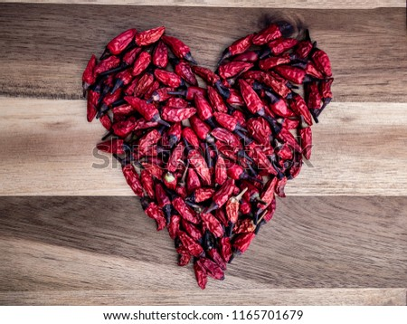 Thai chilies in the shape of a heart on a wooden board #1165701679