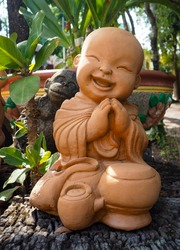 Thai crafts, terracotta statues, Thai novices in a smiling face sitting, paying respect on dry wood.