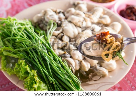 Thai cuisine style, fresh oysters with fried red onion, seafood chili sauce and tamarind.