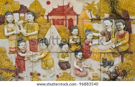 Thai culture of Songkran festival stone carving on temple wall - stock photo