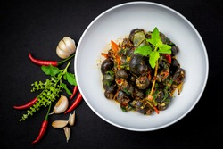 Thai curry with river snail (kaeng hoi khom) Freshwater snail in red curry, chili, fingerroot ginger in white bowl isolated on black background. Thai street food style, top view, dark style