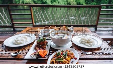 Thai dinner food with rice, Stir fried calamari and shrimp, Chicken soup with coconut milk, chicken grilled BBQ sauce, fried barramundi fishwith herb on the white plate over wooden table in restaurant #1263505927