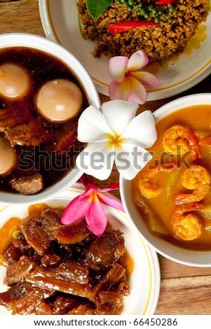 Thai Dinner set,shrimp curry,spicy pork basil,roast pork and pork stew with egg on wood background. - stock photo