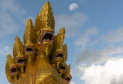 Thai dragon or Naga isolated on blue sky with clouds and moon are background, Selective focus. King of Naga statue symbol of faith in buddhism, can be seen in every temple in Thailand.
