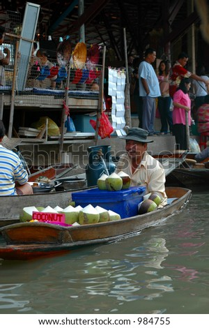 Thai farmer selling coconuts from his boat at a floating market outside Bangkok