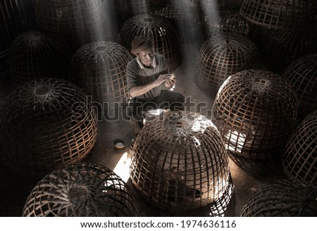 Thai farmer staying in the dark Baan taking care his chick with the sunlight ray in the background Stockfoto ©