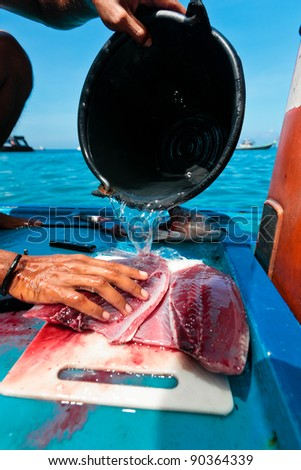 Thai Fishermen cleaning and filleting a fresh tuna aboard a deep sea fishing boat. Prepares tuna sashimi for tourists.