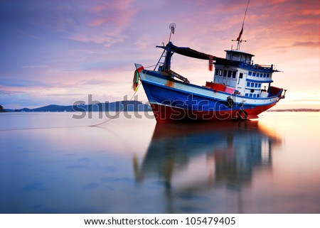 Thai fishing boat used as a vehicle for finding fish in the sea.at sunset