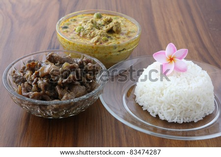 Thai food beef curry and sweet pork with rice in wood background