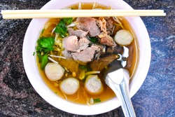 Thai food: beef-noodle soup, mixed meat balls, topped with coriander, along with a rich flavored broth  In a cup with a spoon and chopsticks on the table, black background, top view