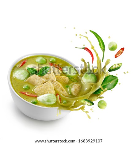 Thai food chicken green curry isolated on white background ,sliced chicken beast fillets, quartered eggplants, pea eggplant, basil leaves ,Kaffir lime leaves and pepper Splash on the air.