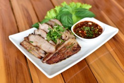 Thai Food Grilled Pork with Thai or Charcoal-boiled Pork Neck with the Sauce is Spicy Sour Taste in a white plate on a wooden table is a Popular Appetizer in Thailand.