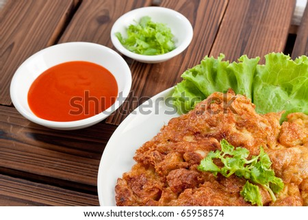 Thai food omelet with Chili sauce on wood background.