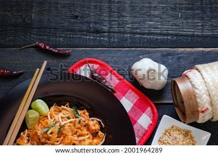 Thai food Pad Thai (Thai national dish) Pad Thai on a black plate with lemon and condiments served on a black wooden table. in thailand.