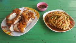 Thai food papaya salad spicy with Sticky rice ,roasting chicken and fresh cabbage  in green wooden table