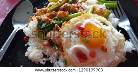 Thai food, rice, kale, pork, fried egg Take pictures using a handheld camera, natural light
