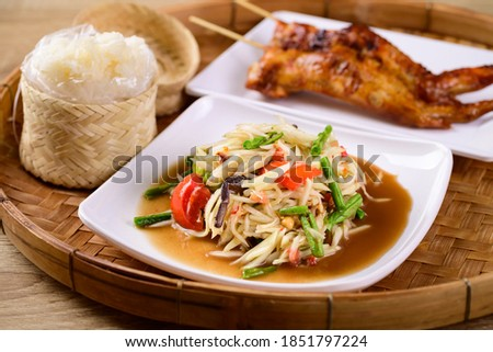 Thai food (Som Tum), Spicy green papaya salad eating with grilled chicken wing and sticky rice on bamboo tray Zdjęcia stock ©