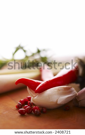 Thai food spices on wooden board (pepper, chili, garlic and lemon grass) - stock photo