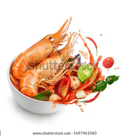 Thai food Tom Yum Kung.Thai hot and spicy soup shrimp in bowl.with Straw Mushroom,lime,Kaffir lime leaves,tomato and chilli. Splash on the air. isolated on white background. Foto stock ©