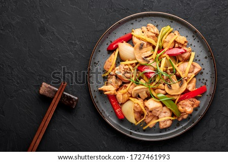 Thai Ginger Chicken or Gai Pad King in dark plate at black slate backdrop. Gai Pad King is Thailand cuisine dish with chicken meat, ginger strips, onion, capsicum and sauces. Thai Food. Copy space