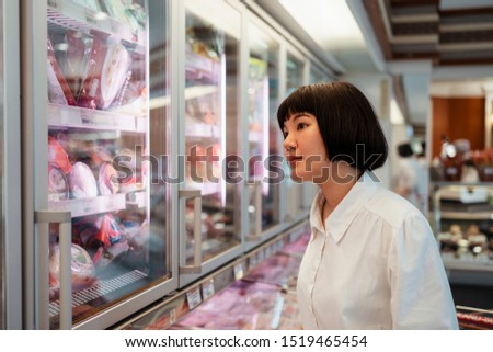 Thai girl looking for some delicatessen from supermarket.