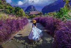 Thai girl wearing a white dress walks the road at Phahee Viewpoint, Mae Sai District, Chiang Rai Province, Thailand