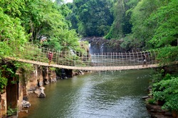 Thai man and woman people travel and posing shooting photo on Suspension wooden and bamboo bridge for cross over stream river at Tad Pha Suam waterfalls in Pakse, Champasak, Laos