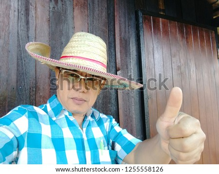 "Thai men wear eye glasses. Wear a hat with bamboo. He wears a blue shirt And the hand made symbol is ""excellent"". #1255558126"