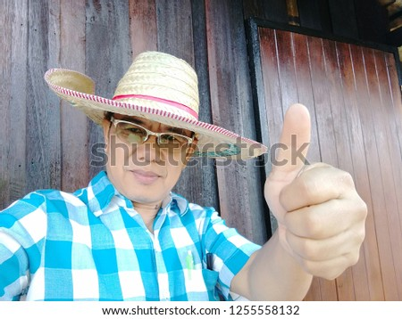 "Thai men wear eye glasses. Wear a hat with bamboo. He wears a blue shirt And the hand made symbol is ""excellent"". #1255558132"