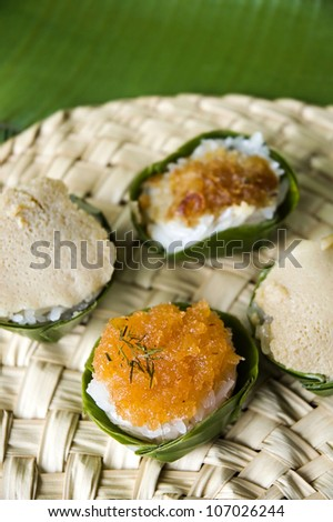 Thai native dessert. Sweet sticky rice with topping in banana leaf cup.