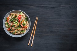 Thai noodle and chicken plate on a black wooden background with Chinese chopsticks and copy space